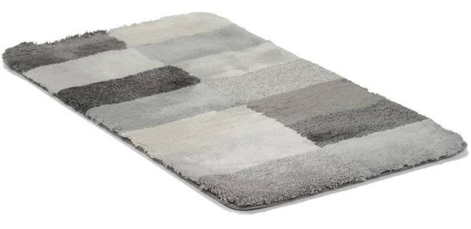 En grå badrumsmatta med stora rutor i olika gråaktiga färger.