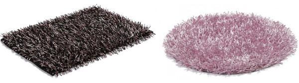 Två badrumsmattor. En ljus rund och rosafärgad, en mörk och rektangulär.
